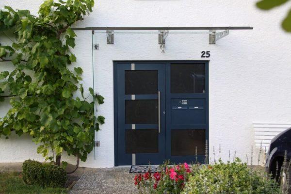 Vordach-in-71065-Sindelfingen-Edelstahl-Glas-Edelstahl-mit-Rundlochmuster-seitliche-Wetterschutz-durch-Glas-Wetterblende-Haustuere-und-Seitenteil-montiert-durch-Fachmonteure